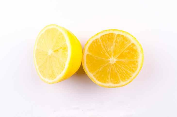 close up photo of sliced yellow lemon on white surface