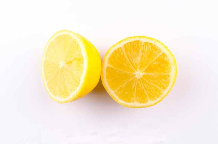 close up photo of sliced yellow lemon on white surface